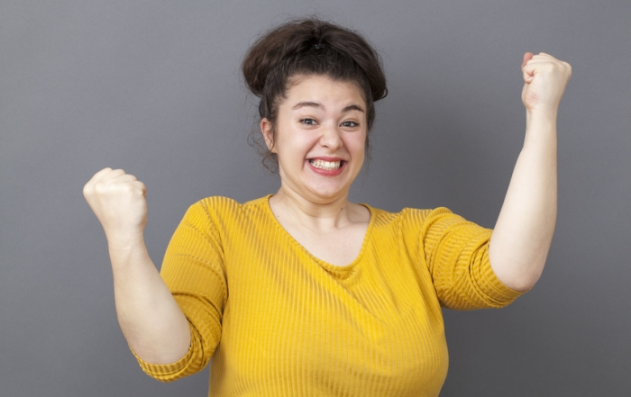 joyful 20s big woman expressing fun victory